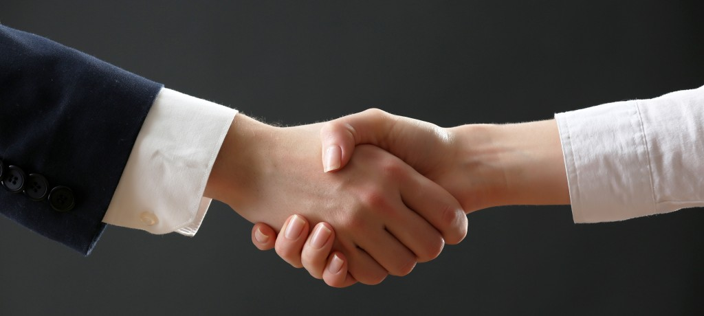 Business handshake on dark background